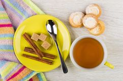 Tea, sugar, cinnamon, teaspoon on saucer, cookies with cottage c. Cup of tea, sugar, cinnamon, teaspoon on saucer, cookies with cottage cheese filling and napkin Royalty Free Stock Photos