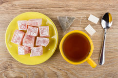 Tea, sugar, tea bag, yellow saucer with rakhat-lukum Royalty Free Stock Images