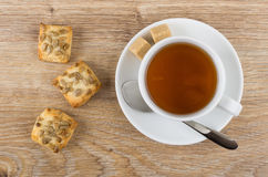 Tea, sugar, teaspoon and cookies with sunflower seeds on table Stock Photos