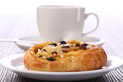 Tea and sweet bun with raisins Stock Images