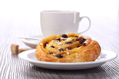 Tea and sweet bun with raisins Stock Photo