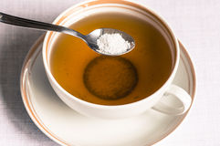 Tea with sweetener in a spoon. Cup of tea with sweetener sorbitol in a spoon Stock Images