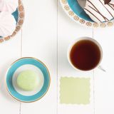 Tea with sweets and card on white background. Selective focus, top view, macro, toned image, film effect. Tea with sweets and card on white background. Selective Stock Images