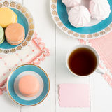 Tea with sweets and card on white background. Selective focus, top view, macro, toned image, film effect. Tea with sweets and card on white background. Selective Royalty Free Stock Image