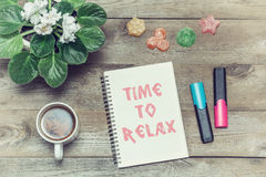 Tea with sweets and an inscription in notebook: Time to relax Royalty Free Stock Photo