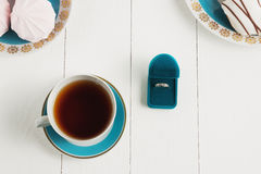 Tea with sweets on a white background whith ring. An offer of marriage, box which give ring. Selective focus, top view, macro, toned image, film effect Stock Images