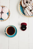 Tea with sweets on a white background whith ring. An offer of marriage, box which give ring. Selective focus, top view, macro, toned image, film effect Royalty Free Stock Photos