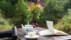 Tea table with a book and flowers stock footage