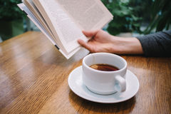 Tea on the table and a book in the hands of men. Tea is on the table and hand a man holding a book Royalty Free Stock Photos