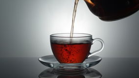 Tea is on the table. Hot tea is poured into a mug from a teapot stock footage