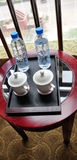The tea table of hotel. The tea table of the hotel on the cups and mineral water bottles Royalty Free Stock Photography
