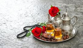 Tea table red rose flowers dates Islamic holidays decoration. Tea table with red rose flowers and dates. Islamic holidays decoration. Ramadan kareem Stock Photos