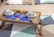 Tea table with white cups and blue petals royalty free stock image