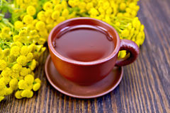 Tea from tansy in clay cup on board. Herbal tea in a clay cup of fresh tansy flowers on the background of wooden boards Royalty Free Stock Images