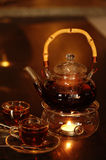 Tea and Teapot. Teapot with a candle boiler and teacups, contain fruit tea Royalty Free Stock Images