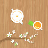 Tea teapot and a branch of the cherry blossoms . Tea teapot and a branch of the cherry blossoms on a wooden table. Vector illustration Stock Image