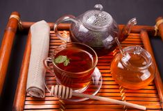 Cup of tea with teapot, honey in oriental style on a wooden tray stock image