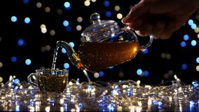 Tea from the teapot is poured into glass small cup stock footage
