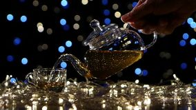 Tea from the teapot is poured into small glass cup, slow motion stock footage