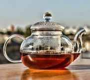 Tea. Teapot with tea. Breakfast. Tea in a glass teapot on the background of the modern city. Summer time Royalty Free Stock Photo