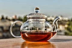 Tea. Teapot with tea. Breakfast. Tea in a glass teapot on the background of the modern city. Summer time Stock Photography