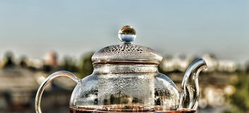 Tea. Teapot with tea. Breakfast. Tea in a glass teapot on the background of the modern city. Summer time Stock Photo