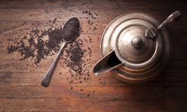 Tea Teapot Wood Background. An old teapot with teaspoon and loose-leaf black tea on a rustic wood background photographed from above Stock Photo