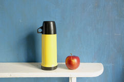 Tea thermos and red apple on wooden shelf Royalty Free Stock Image