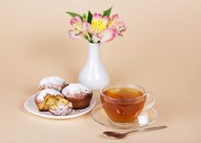 Tea-things, cupcakes and vase with flowers Stock Image