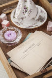 Tea things with sweets and postcards on the wooden tray vertical Royalty Free Stock Image