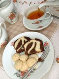 Tea time - 1. A table set for tea, with tea being poured and a plate of cake and cookies stock photos