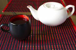 Tea time. Cap of tea and teapot on bamboo mat Royalty Free Stock Image