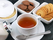 Tea time. A cup full of hot tea and many delicious cookies and biscuits royalty free stock image