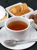 Tea time. A cup full of hot tea and many delicious cookies and biscuits stock images