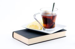 Tea time. A cup tea with the bag, and lemon and a book Stock Photo