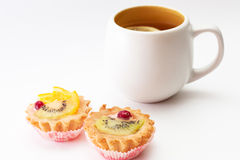 Tea time. A couple of tart lets and a cup of tea with lemon Stock Image