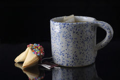 Tea Time. A mug with a blue pattern, holds a cup of tea. There is a cookie sitting next to the cup.  The cup and cookie sit on a black background Stock Photography
