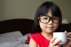 Tea time. Portrait of a little girl wearing spectacles and hold a cup in hotel room Stock Photography