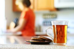 Tea time. Woman working in her kitchen. Tea and cookies waiting stock photography