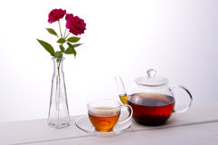 Tea time. Tea and red roses on white background Stock Photo