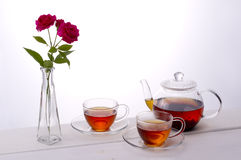 Tea time. Tea and red roses on white background Stock Image