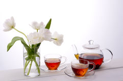 Tea time. Tea and white tulips on white background Royalty Free Stock Images