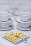 Tea time. A lot of white cups for tea and coffee and a slices of lemon on the table in the hotel Royalty Free Stock Images