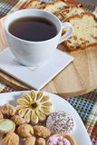 Tea-time. Cookies, cup of tea and cake slices Stock Photos