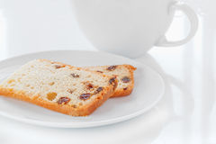 Tea Time. Two Slices of Sultana Cake on a White Plate with a Tea Cup Royalty Free Stock Photo