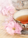 Tea Time with Antique Japanese Teacup. Closeup of a vintage Japanese teacup with pink cherry blossoms and bamboo placemat stock photo