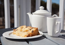 Tea time on the balcony. A cup of tea and a slice of fruit cake served on a balcony Stock Photo