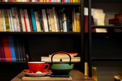 Tea time in book shop. Tea pot and cup on the wooden table. stock photo
