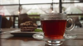 Cup of hot tea with smoke in transparent cup on saucer in cold room with cake. stock video