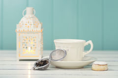 Tea time. A candle, a white cup, a tea infuser and a shortbread on a white wooden table. Vintage scene Royalty Free Stock Image